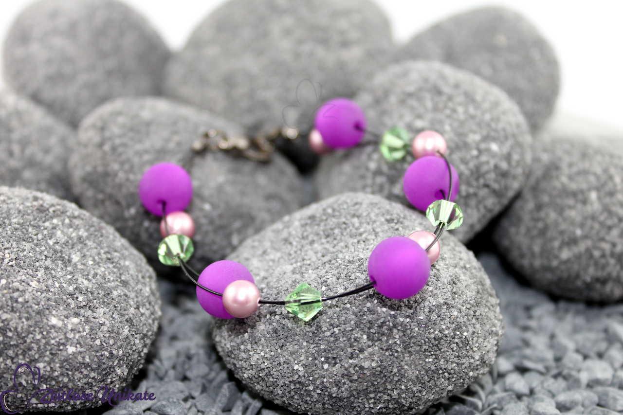lila, rosa, grün auf schwarz - interessanter Armschmuck