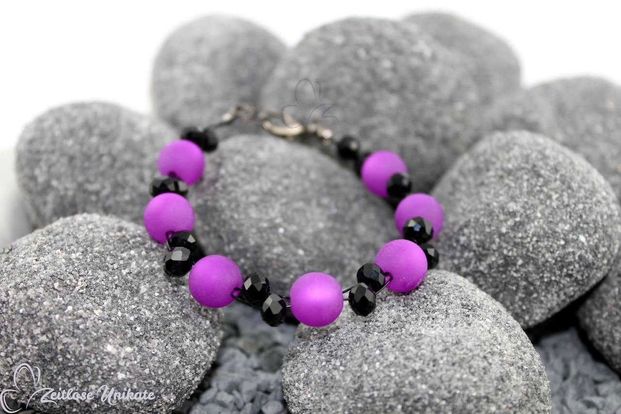 lila schwarzes Armband dient als Beispiel für Armschmuck in dunkel rosa schwarz
